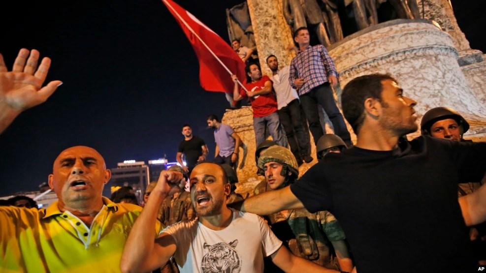 Les partisans du président Recep Tayyip Erdogan protestent devant des soldats sur la place Taksim d'Istanbul, 16 juillet 2016.