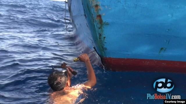Một ngư dân Việt Nam sửa chữa chiêc tàu bị tàu hải giám Trung Quốc đâm vào