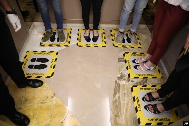 Para pengunjung berdiri di tempat yang sudah ditandai dalam sebuah lift untuk menjaga jarak aman sebagai upaya mencegah penularan virus corona, Surabaya, 19 Maret 2020. (Foto: AP)