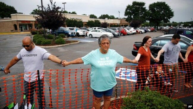 Lisa Dunaway (centro), residente de Virginia Beach, Virginia, se da la mano con recolectores de basura de la ciudad durante una vigilia en respuesta a un tiroteo en un edificio municipal. 1 de junio de 2019.
