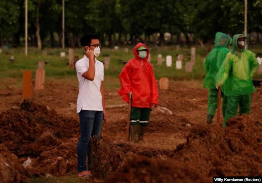 Firos Justin Sumantri, putra Ratih Purwarini, seorang dokter yang meninggal karena COVID-19, berdoa saat petugas kota menunggu, di samping makam ibunya saat pemakaman di Jakarta, 31 Maret 2020. (Foto: REUTERS/Willy Kurniawan )