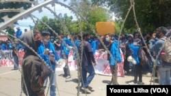 Polisi mengamankan seorang mahasiswa dalam unjuk rasa penolakan UU Cipta Kerja oleh mahasiswa Kota Palu yang berakhir bentrok dengan aparat keamanan. Kamis, 8 Oktober 2020. (Foto: VOA/Yoanes Litha)
