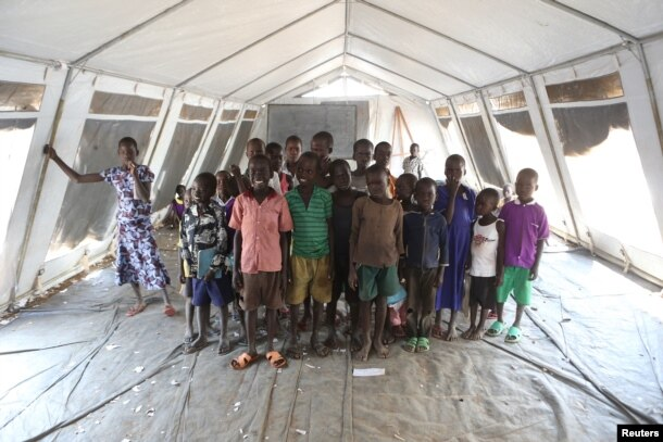 Children, who fled fighting in South Sudan, stand inside a tented classroom at the Bidibidi refugee resettlement camp near the border with South Sudan, in northern Uganda, Dec. 7, 2016.