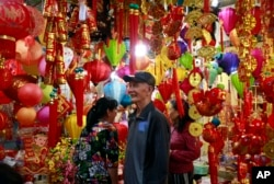 In this Sunday, Feb. 3, 2019, photo, people shop for decorative ornaments in Hanoi, Vietnam. Vietnam is celebrating the Lunar New Year of the Pig, the biggest annual festival of the year. (AP Photo/Hau Dinh)