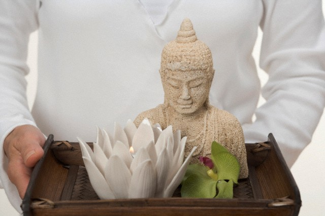07 Mar 2008 --- Woman holding Buddha statue, candle and orchid on tray --- Image by © the food passionates/Corbis