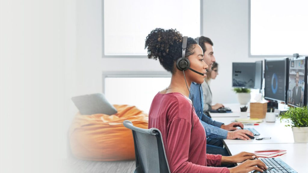 woman using Logitech zone wired headset in office at computer desk with colleagues