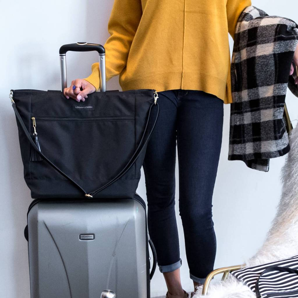 A woman ready for a trip with her suitcase and her Logan + Lenora Weekender bag.