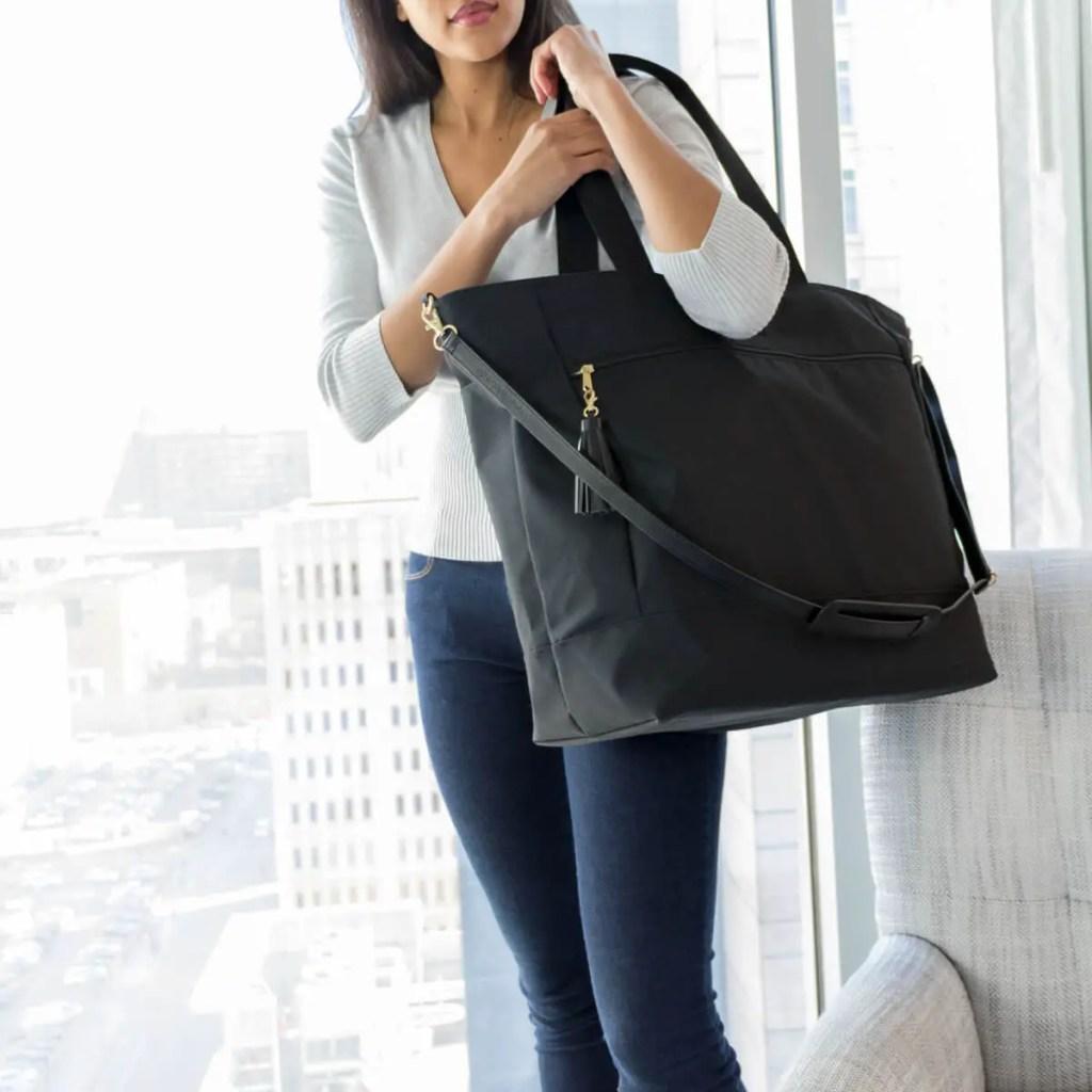 A woman holding her Logan + Lenora Weekender bag.