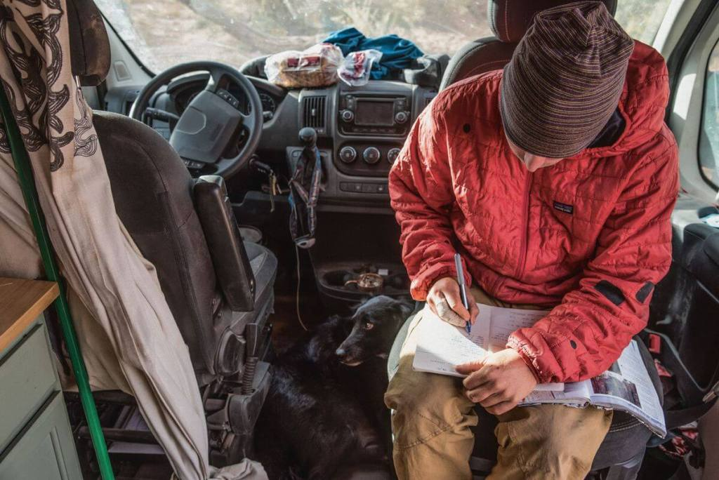 A man in his car wearing his Patagonia men's Nano Puff Jacket as he gets ready to explore.