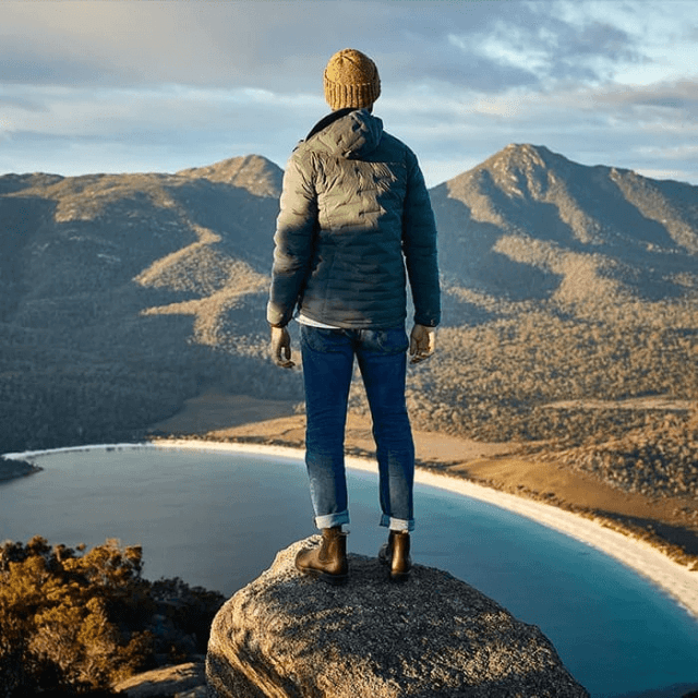 A woman wearing her Blundstone boots on the top of a mountain.