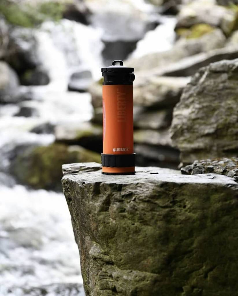 An orange LifeSaver Liberty Bottle sitting on a large stone next to a waterfall and stream.