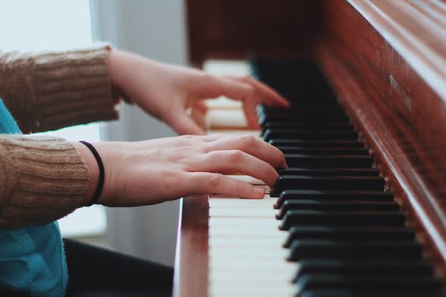 A close-up of a girl's hands as she plays piano