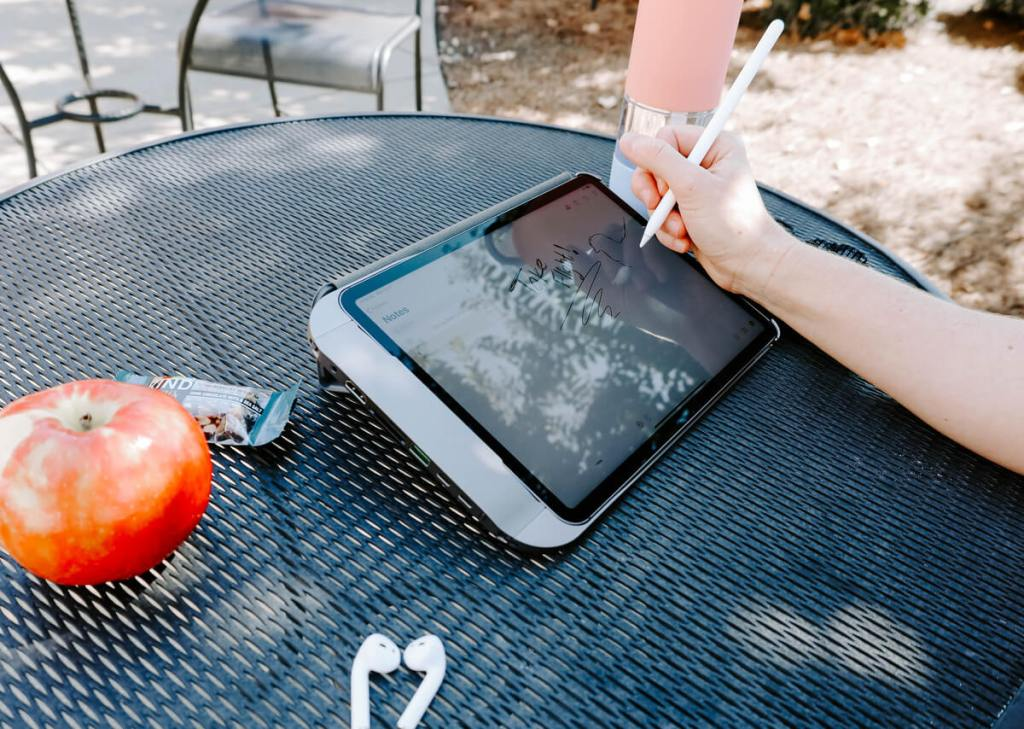 Someone sitting at a picnic table using their iPad Pro while utilizing their Hubble iPad case.