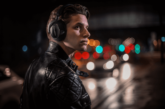 A man wearing his Bowers & Wilkins PX7 Carbon headphones in the city at night.