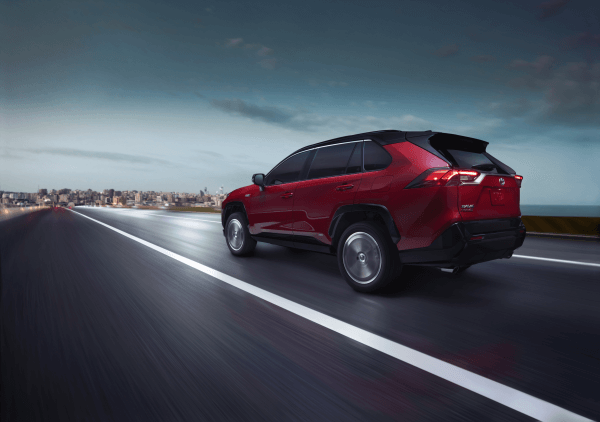 A red 2021 Toyota RAV4 Prime XSE Premium driving down a road into a city.