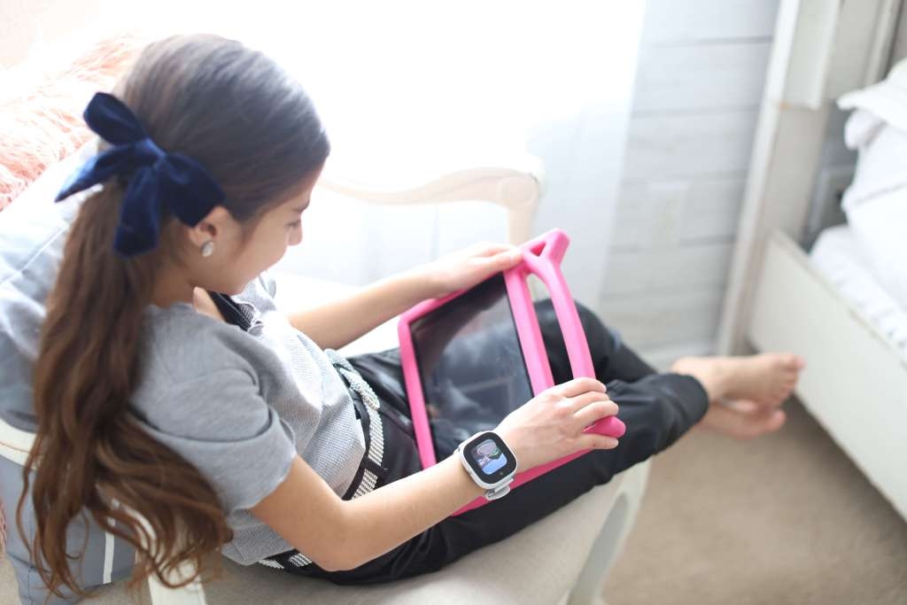 A little girl playing on her tablet wearing the GizmoHub Verizon watch Disney Edition.