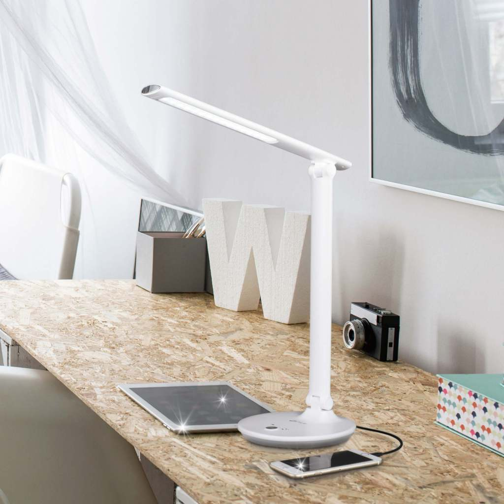 The OttLite lamp on a desk and lit over an iPad and iPhone