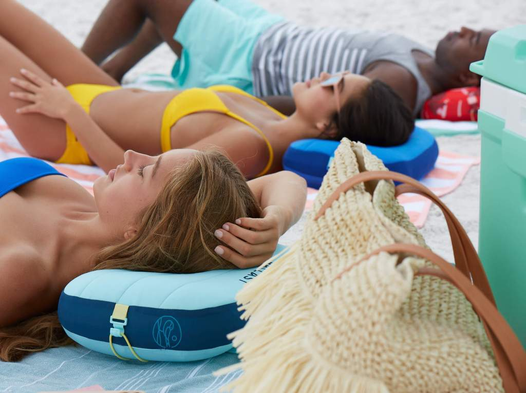 A group of people laying on the beach while resting their heads on their comfy Ballast pillows.