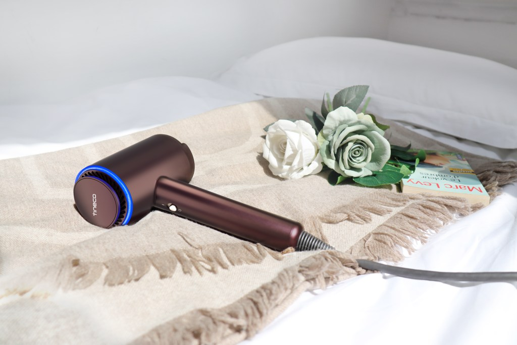 The Moda One blow dryer laying on a blanket with some roses and a book.