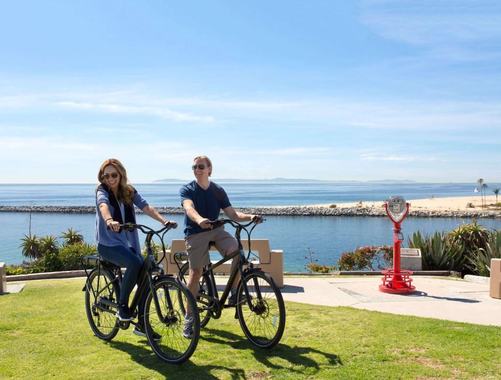 a couple riding their Pedego electric. bikes on the Hello Fun Tour.