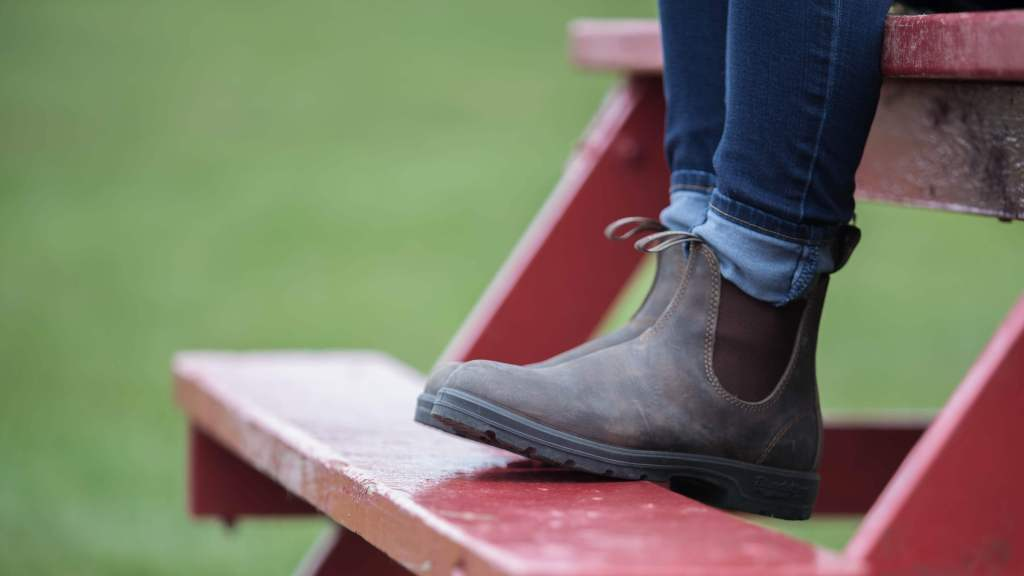 A girl wearing her Blundstone Boots as she sits on a bright red picnic table.