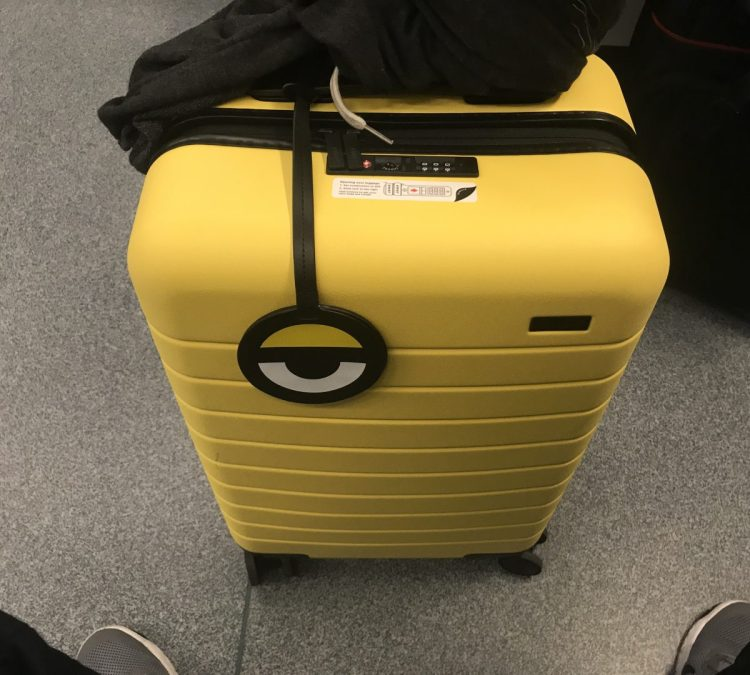 your carry on luggage will stand out with away s new minion yellow suitcase geardiary. Black Bedroom Furniture Sets. Home Design Ideas