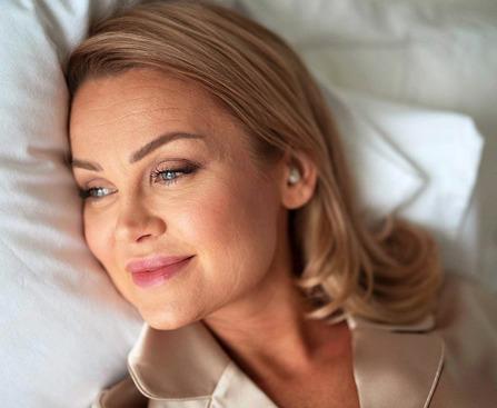 Woman wearing QuietOn 3 sleep earbuds in bed.