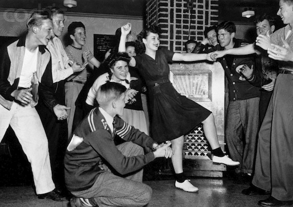 ca. 1955-1960 --- Young couple dance while a crowd of friends cheer them on. --- Image by © Keystone/Corbis
