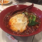 Spicy noodle dish with fried egg and bok choi in a red bowl.