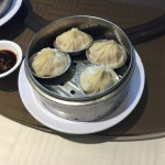 Four Xiao Long Bao served in aluminum cups and these served in a metal steamer on a white dish.