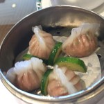 Steamed shrimp and veg dumplings served with slices of zucchini on paper within a metal steamer basket.