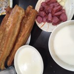 Large Twisted Crullers served on a very small plate, Taiwan Sausage cut in slices and served on a circular plate, and two white bowls of hot, unseasoned soy milk.