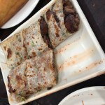 Beef roll cake served on a white rectangular serving dish.