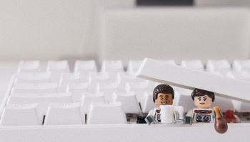 Two Lego mini-figs poking out from a computer keyboard