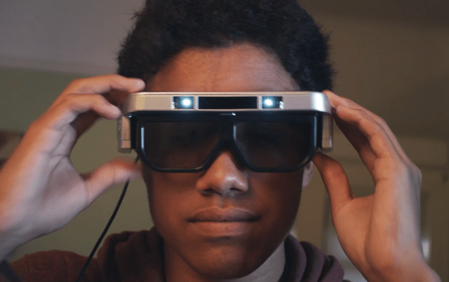 A man wears the Cast AR glasses. His hands lightly touch the glasses on the arms. Twin projectors emit light above his eyes.