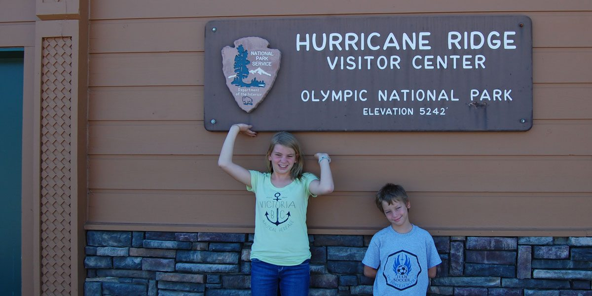 Family tradition: a photo of the kids by the sign at a National Park. Photo by Rob Huddleston