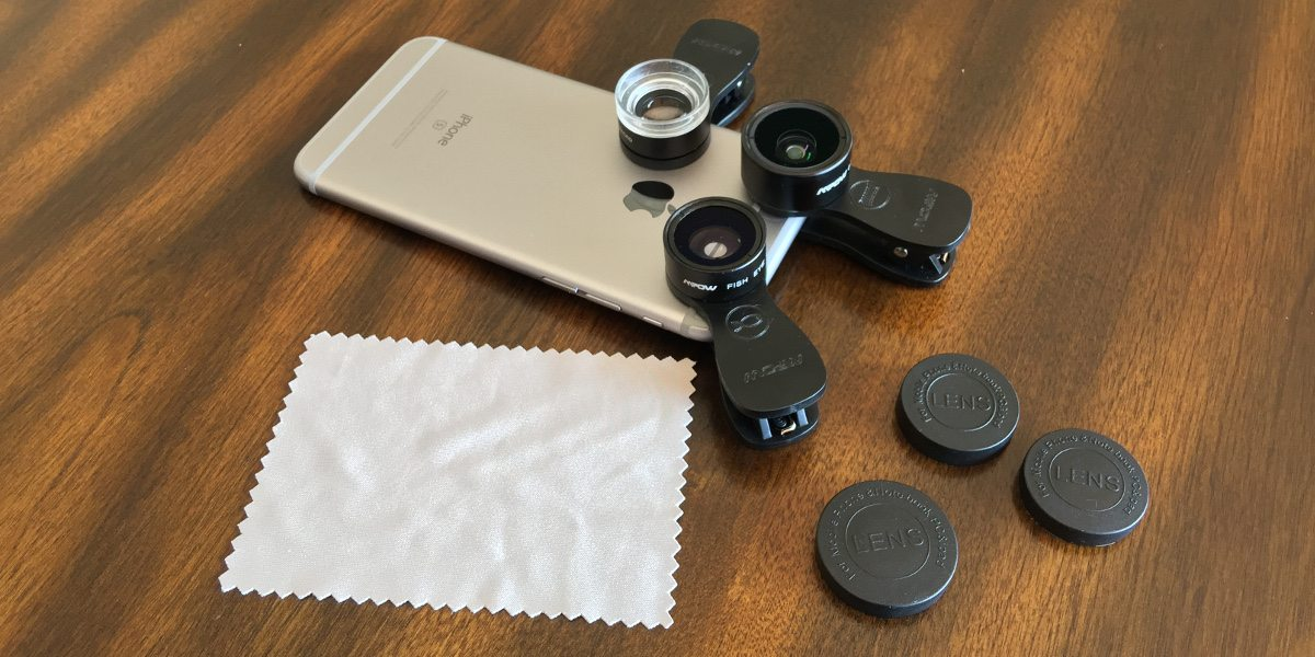 An iPhone with the three clip-on lenses attached, also showing the lens caps and cleaning cloth.
