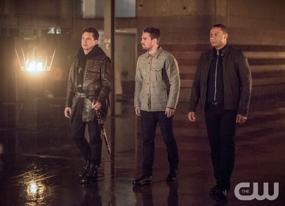 "Arrow -- ""Sins of the Father"" -- Image AR413b_0007b.jpg -- Pictured (L-R): John Barrowman as Malcolm Merlyn, Stephen Amell as Oliver Queen, and David Ramsey as John Diggle -- Photo: Dean Buscher/ The CW -- �© 2016 The CW Network, LLC. All Rights Reserved."