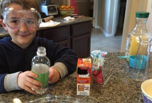 Child with ingredients for science fair project.