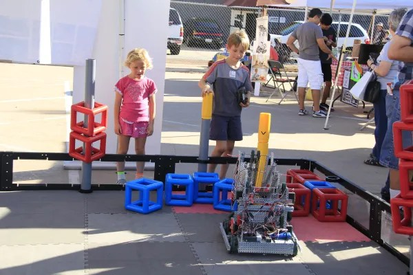 Several children looking at a small wheeled robot performing a programmed task