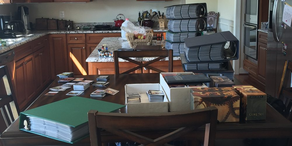 Binders of Magic: The Gathering cards stacked on top of each other; over 7 of them, in a kitchen on the table and the counter.