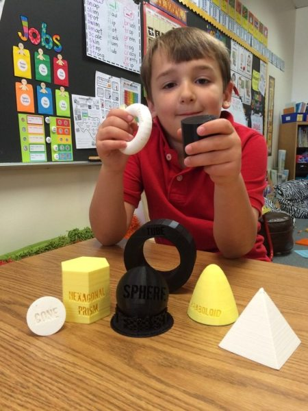 1st grader holds two 3D shapes while others sit on a table in front of him