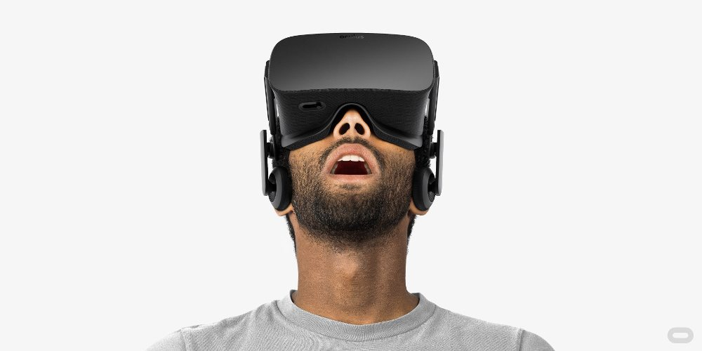 Bearded man looks up with his mouth open wearing a VR headset.