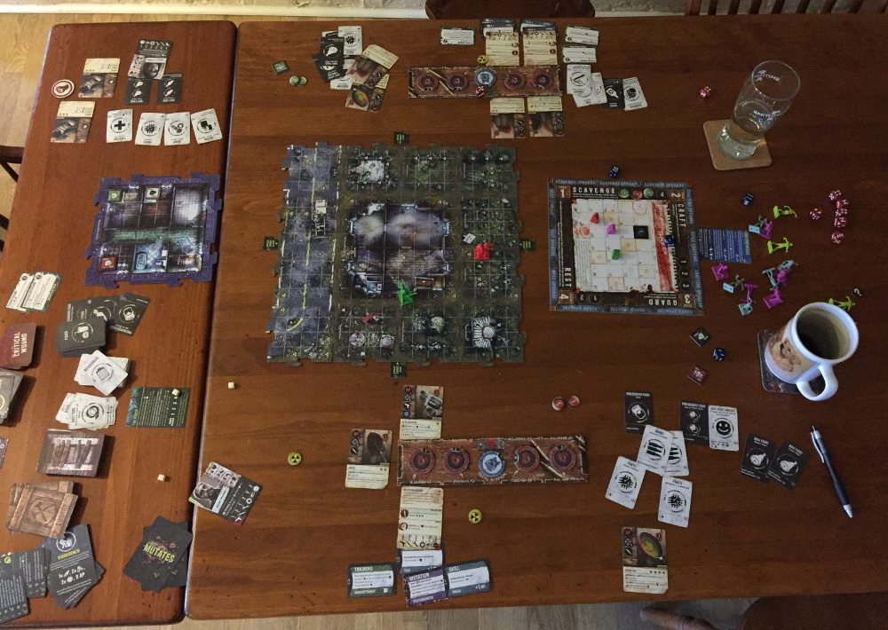 A large table (6' long at least) covered in a game of Zpocalypse 2.