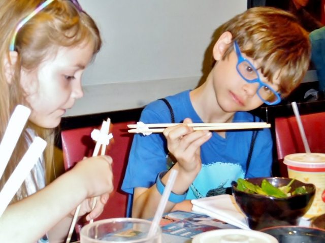 Two blond children trying chopsticks at Teppan Edo in EPCOT