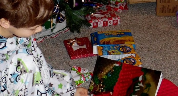 Boxes of mac and cheese beside a boy under a christmas tree