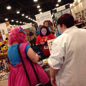 Arbitrary Muse working at a con! Photo provided by Emily Willis and Ann Uland.