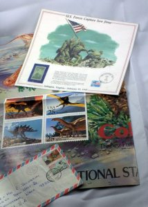 Bits and pieces of a stamp collection: a poster with dinosaur stamps, a commemorative Iwo Jima stamp, and an envelope with stamps from South Africa.