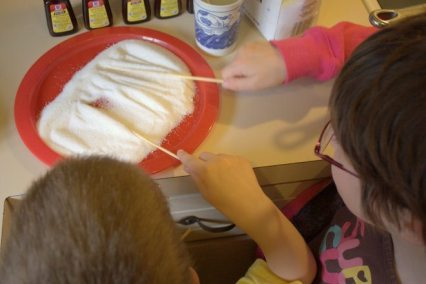 The kids rolling wet skewers in sugar to set aside and dry.