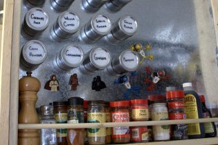 The spice rack. Our geeky magnets are hanging out too. We keep the spices we use most in the magnetized containers and the others on the shelf. If the spices we use change, we can wipe off the container and write something else with a wet wipe pen.
